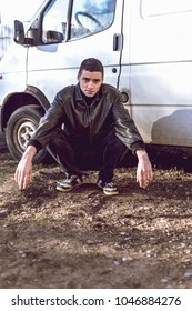 A young guy of criminal appearance in a black leather jacket stands near an old white van.