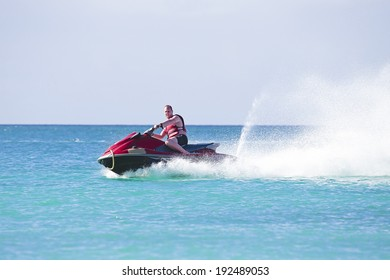 Young guy cruising on a jetski on the caribbean sea
