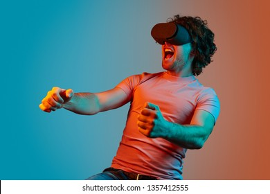 Young guy with curly hair screaming and driving virtual car while playing VR racing game under blue and orange light