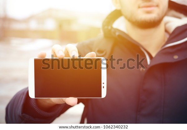 A young guy demonstrates a smartphone display on the background of a big house in winter. Copy space for text