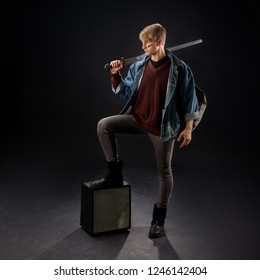 A young guy in a denim jacket put his foot on the subwoofer. Dreamy fantasy character holding a sword on the shoulder