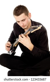 a young guy dressed in black clothes sits and plays the guitar isolated on white background