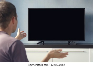 A young guy emotionally watching TV and waving his hands in discontent. Blank screen for design. Frustrated Man Sitting On Sofa In Front Television With No Signal.