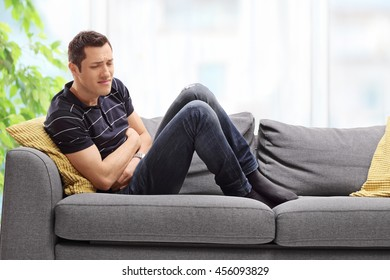 Young guy experiencing stomach pain seated on a couch at home