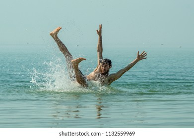 A young guy falls into the sea water, a beautiful spray