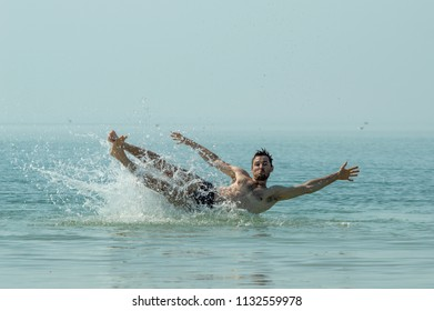 A young guy falls into the sea water, splashes of water drops