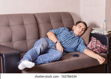 A young guy fell asleep on the couch while watching TV