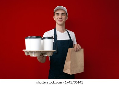 young guy a food delivery uniform in uniform gives coffee and a package on a red background, delivery service worker