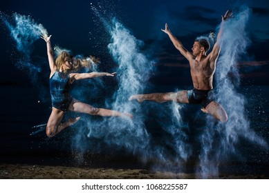Young guy and girl in black swimwear high jump and dance on the beach in the evening. Street ballet. Flour, talc, dust.