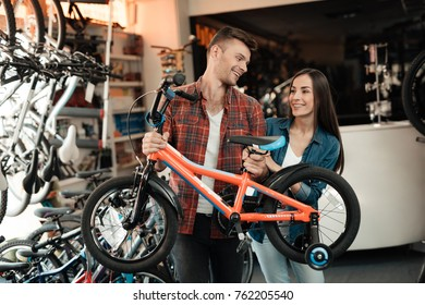 A young guy and a girl are choosing a children's bicycle. They are in a bicycle shop. They are in a very good mood.