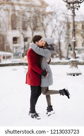 A young guy and a girl are hugging each other. Winter. A park.