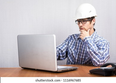 young guy with glasses at the Desk on the table laptop and phone