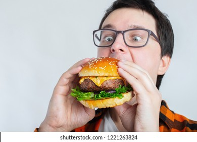 A young guy with glasses holding a fresh Burger. A very hungry student eats fast food. Hot helpful food. The concept of gluttony and unhealthy diet. With copy space for text.