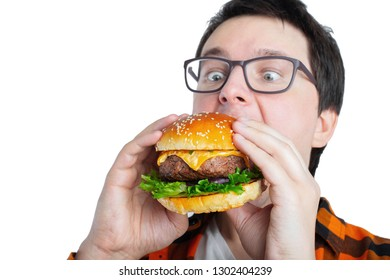A young guy with glasses holding a fresh Burger. A very hungry student eats fast food. Hot helpful food. The concept of gluttony and unhealthy diet. With copy space for text. Isolated.