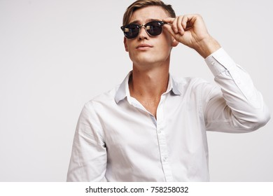 young guy with glasses looks up.