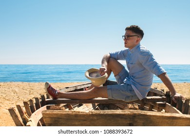 A young guy in glasses relax on the beach. He is sitting in the old boat. He is holding hat on his hand and looking dreamly far away.