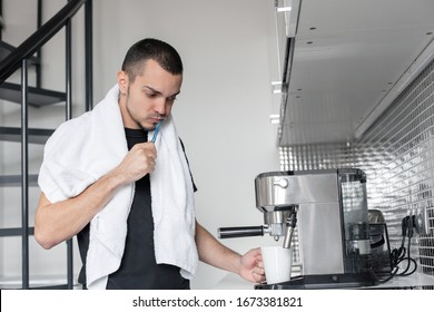 A young guy is going to work in the morning. Brushes teeth near a coffee machine while waiting for a cup of coffee.