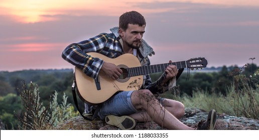young guy with guitar outdoors at sunset, music and travel concept