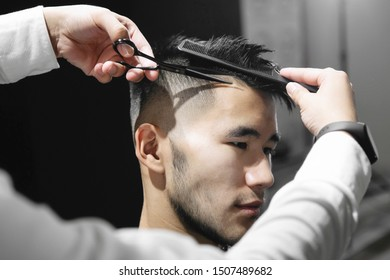 Young guy hairdresser cuts hair with scissors to a man in a beauty salon.