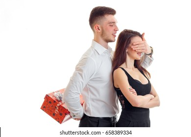 young guy has closed girl eyes and keeps behind gift