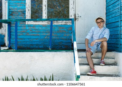 A young guy in a hat and glasses is in the old village. He sits on the steps of one of the houses and looks dreamily.
