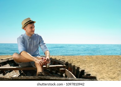 A young guy in hat is relax on the beach. He is sitting in the old boat. He is smilling and looking dreamly far away.