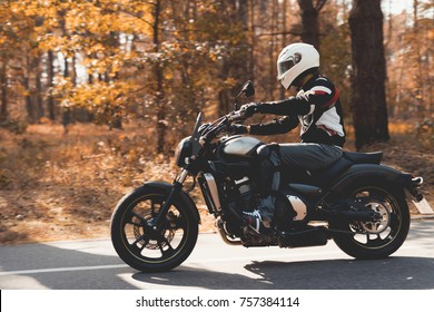 A young guy in a helmet is riding on a forest road on an electric motorcycle. He sits confidently in the saddle. There are green trees around him.