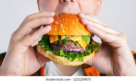 A young guy is holding a fresh Burger. A very hungry student eats fast food. Hot helpful food. The concept of gluttony and unhealthy diet