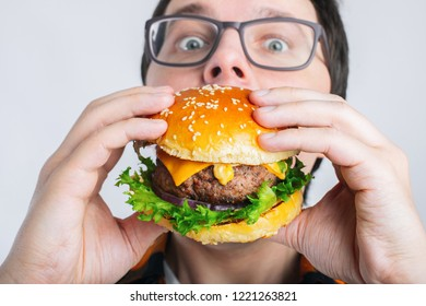 A young guy is holding a fresh Burger. A very hungry student eats fast food. Hot helpful food. The concept of gluttony and unhealthy diet.