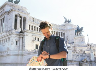 A young guy holds a map in his hands and look at his watch on a beautiful sunny day. Rome, Italy. The famous Vittorio Emanuele II monument at Piazza Venezia in Rome, Italy