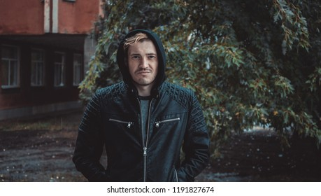 a young guy in a hood standing on the street on a cloudy day. emotional portrait of a student. street style: leather jacket and shirt
