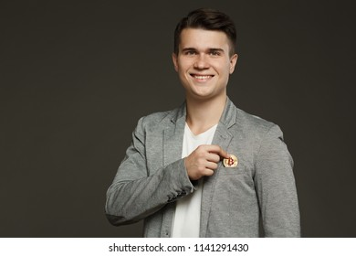 A young guy in a jacket puts a coin bitcoin in his pocket on a gray background.