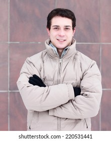 The young guy in a jacket standing in winter.