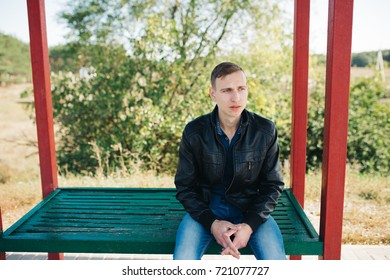 young guy in jeans standing at the bus stop waiting for my bus. emotional portrait. short hair and troubled skin. posing outside, autumn day