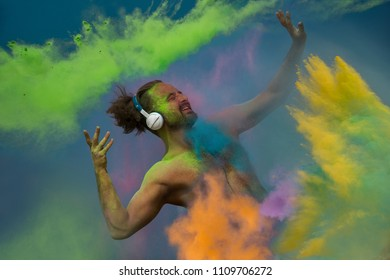 Young guy listening music in headphones in the fog of colors during Holi celebration