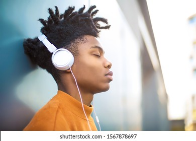 Young guy listening music with the headphones, leaning on the wall