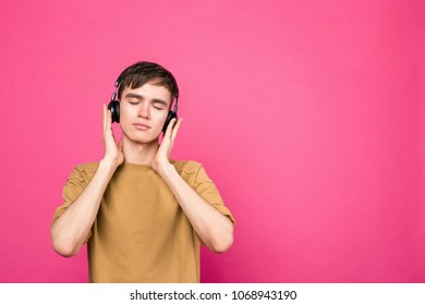 Young guy listening to music in wireless headphones standing on pink background