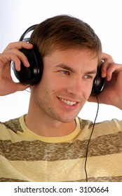 young guy listens to music in headphones and looks aside