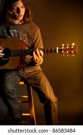 A young guy with long hair playing an acoustic guitar with golden light