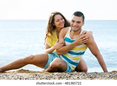 Young  guy and long-haired girl  spending free time at seaside in sunny day