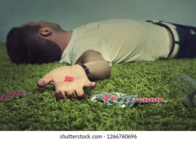 A young guy is lying dead on the floor of an apartment with red pills in his hand. The concept of poisoning and suicide. death by drug overdose.