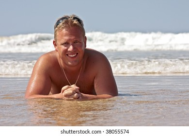 Young guy lying in the water from the atlantic ocean relaxing and smiling,