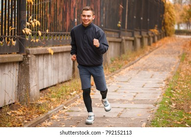 A young guy makes a light jog in the autumn park. The concept of sport.