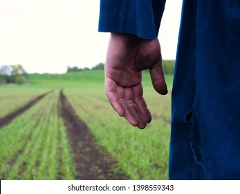 A young guy (man), a farmer in a working uniform, walks across a field in rubber boots. Concept of: Freedom, Rubber boots, Lifestyle.