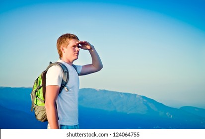 young guy is in the mountains and looks into the distance