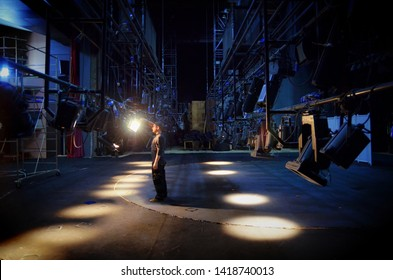 A young guy mounts lighting equipment on the stage of the theater