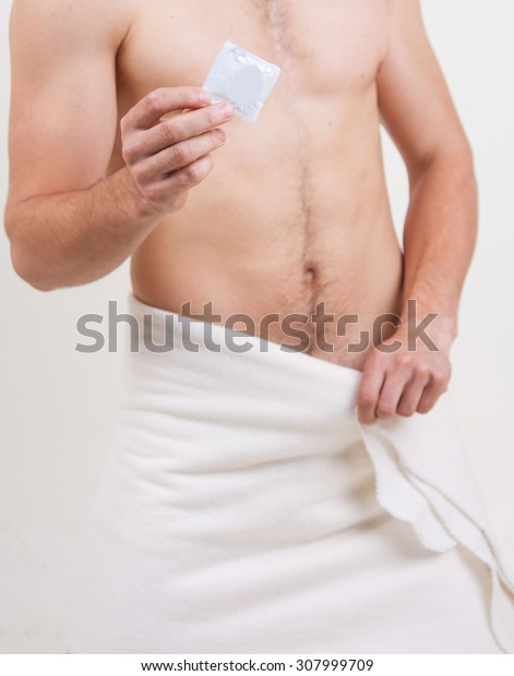 A young guy with a naked torso and a towel around her waist holding a condom. Protected sex.