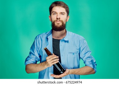 Young guy on a green background holds a bottle of beer, alcohol.