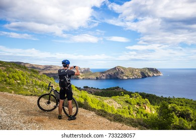 a young guy on a mountain bike trails in Spain and takes a photo on a white phone in the background of the  sea of the rocky coast of the Costa Brava. In a blue helmet and a black backpack.