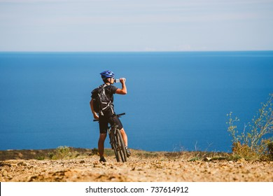 a young guy on a mountain bike stopped to drink water from a jar on a stony road near the Mediterranean Sea in Spain. Active tourism in Europe